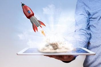 Mans hand holding tablet pc with rocket launching off surface.