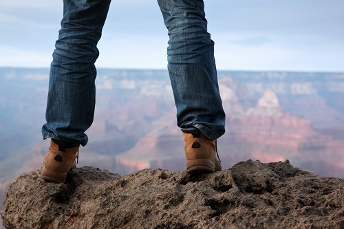 Man standing on the edge of a cliff looking out at a beautiful canyon and the horizon.